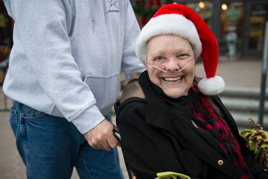 Glenda Seitz cracks a smile while wearing a Santa hat before visiting Santa Claus in Old Town Square on Wednesday, December 12, 2018. Glenda, in hospice care after four years of cancer, had never sat on Santa's lap.