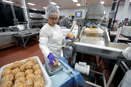 Eva Vargas does weight control of sharp cheddar cheese balls at Kaukauna Cheese  in Little Chute.