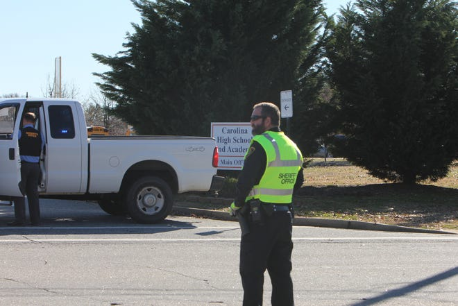 A Greenville County Sheriff's Office deputy stands on State 81 outside of Carolina High School and Academy.
