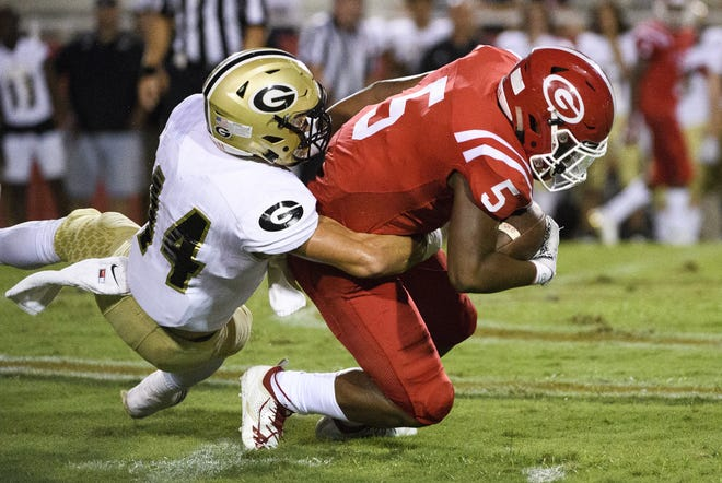 Greer's Ethan Alexander (14) brings down Greenville's Reggie Norris in a Sept. 28 game. Alexander was defensive MVP for the North in the Touchstone Energy Bowl.