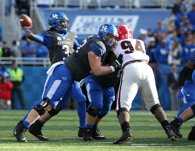 Kentucky offensive lineman Mason Wolfe, center, blocks Georgia's Michael Barnett while quarterback Terry Wilson attempts a pass during the Wildcats' 34-17 loss on Nov. 3 in Lexington.