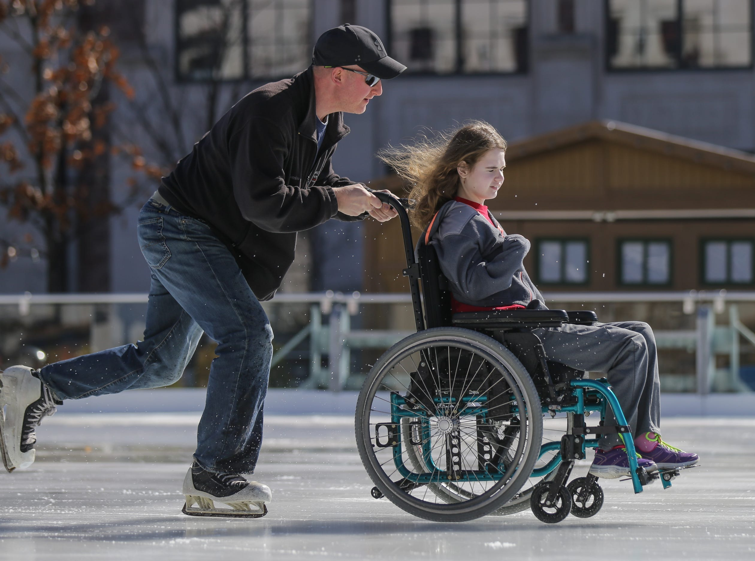 Former college hockey player David Weninger pushes his daughter Lauryn Weninger around The Ice at Center Green skating rink during a special needs afternoon skating session in Carmel Ind. on Monday, Feb. 26, 2018.