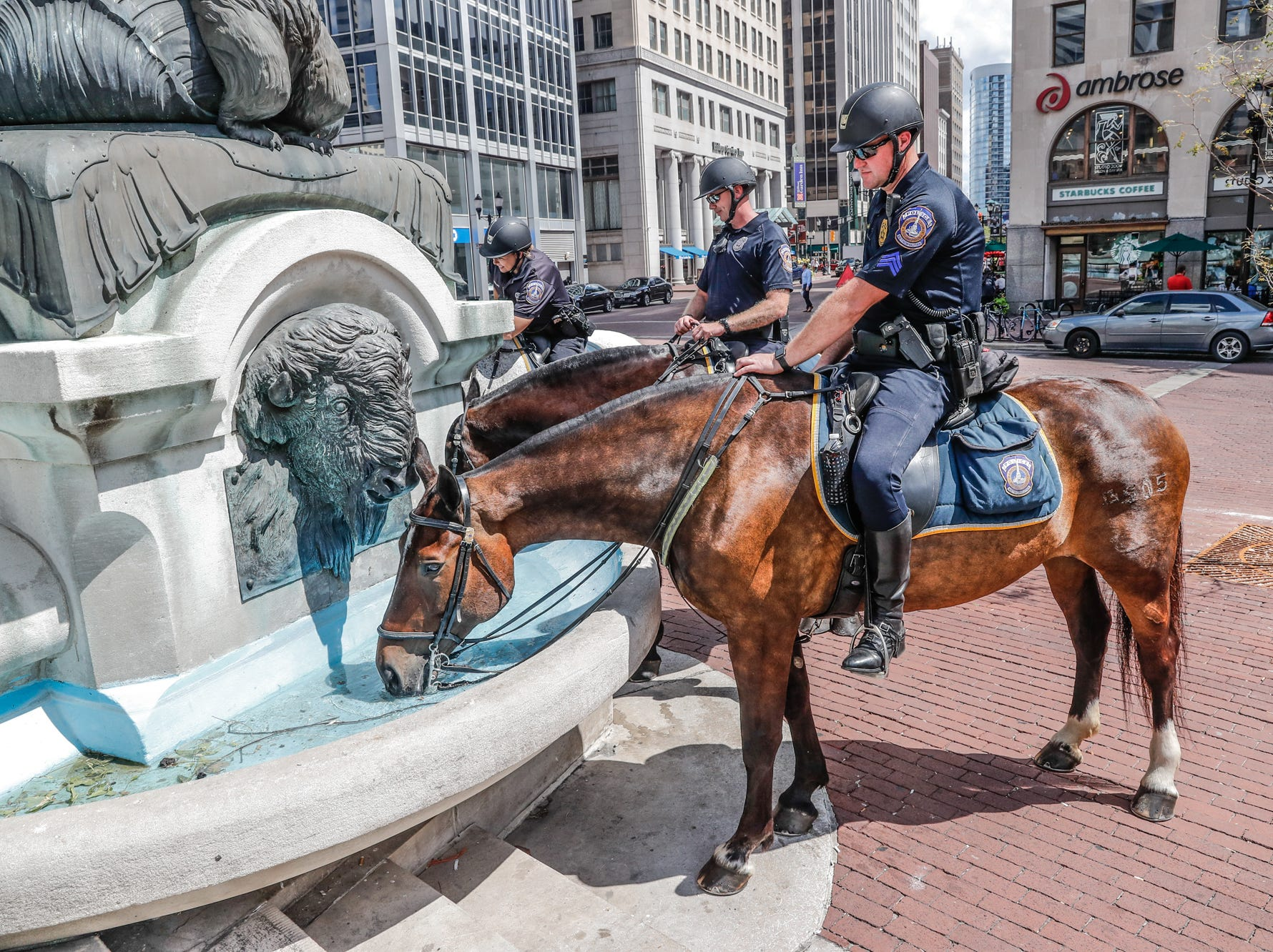 IMPD Mounted Patrol officers, front to back, Sgt. Allan Whitesell, Chad Pryce, and Lorie Phillips stop to water their horses, Maddie, Ramsey, and Cody at the Soldiers and Sailors Monument fountains on a near ninety degree day in downtown Indianapolis on Tuesday, Sept. 4, 2018.
