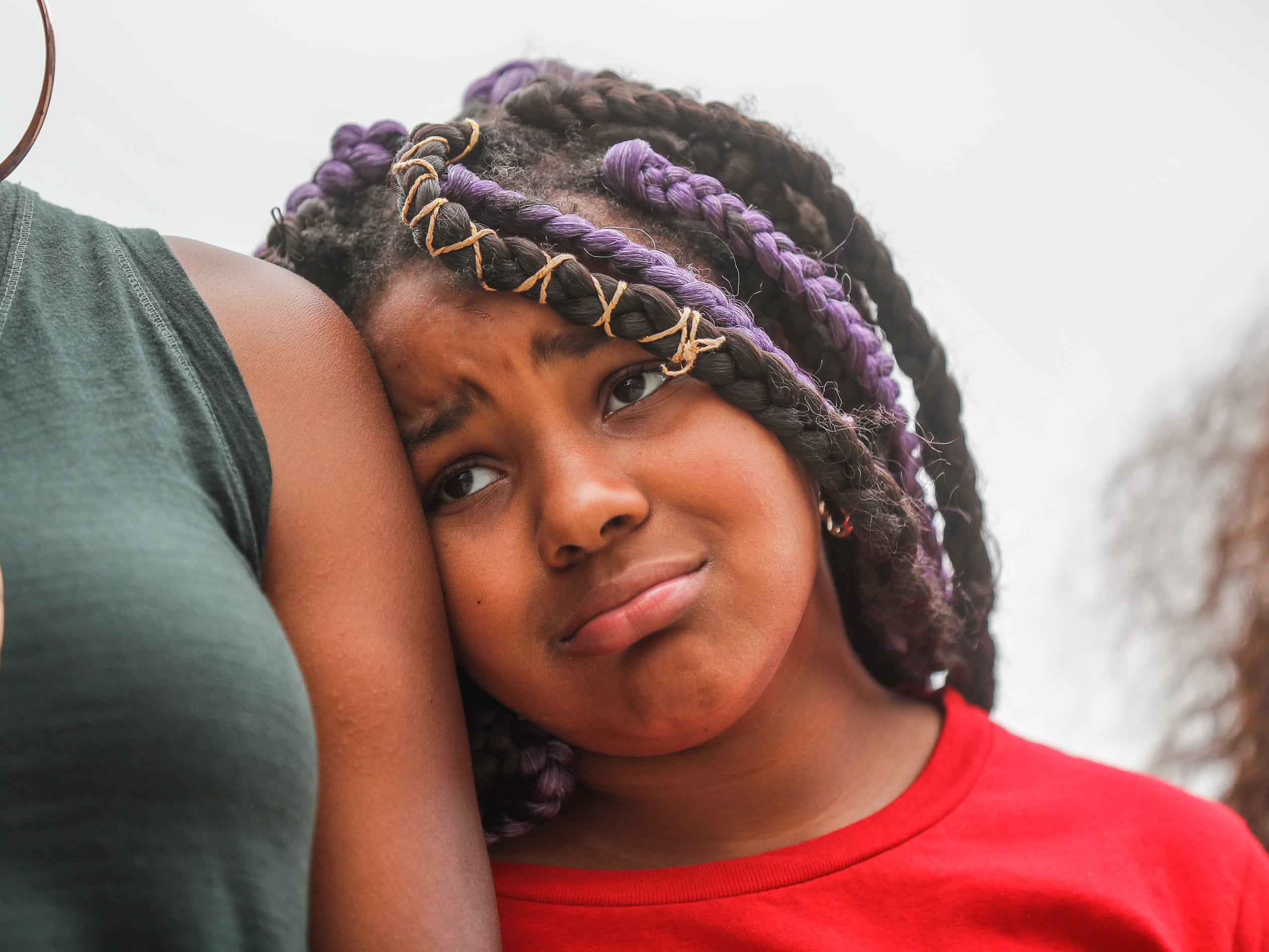 Ashlynn Davis leans on her mother while attending the 'We Live' Peace Walk and community day to end youth violence at Washington Park. on Saturday, Aug. 11, 2018. 'We Live,' which stands for 'Linked To Intercept Violence' was started by students from Warren Central High School in Indianapolis.