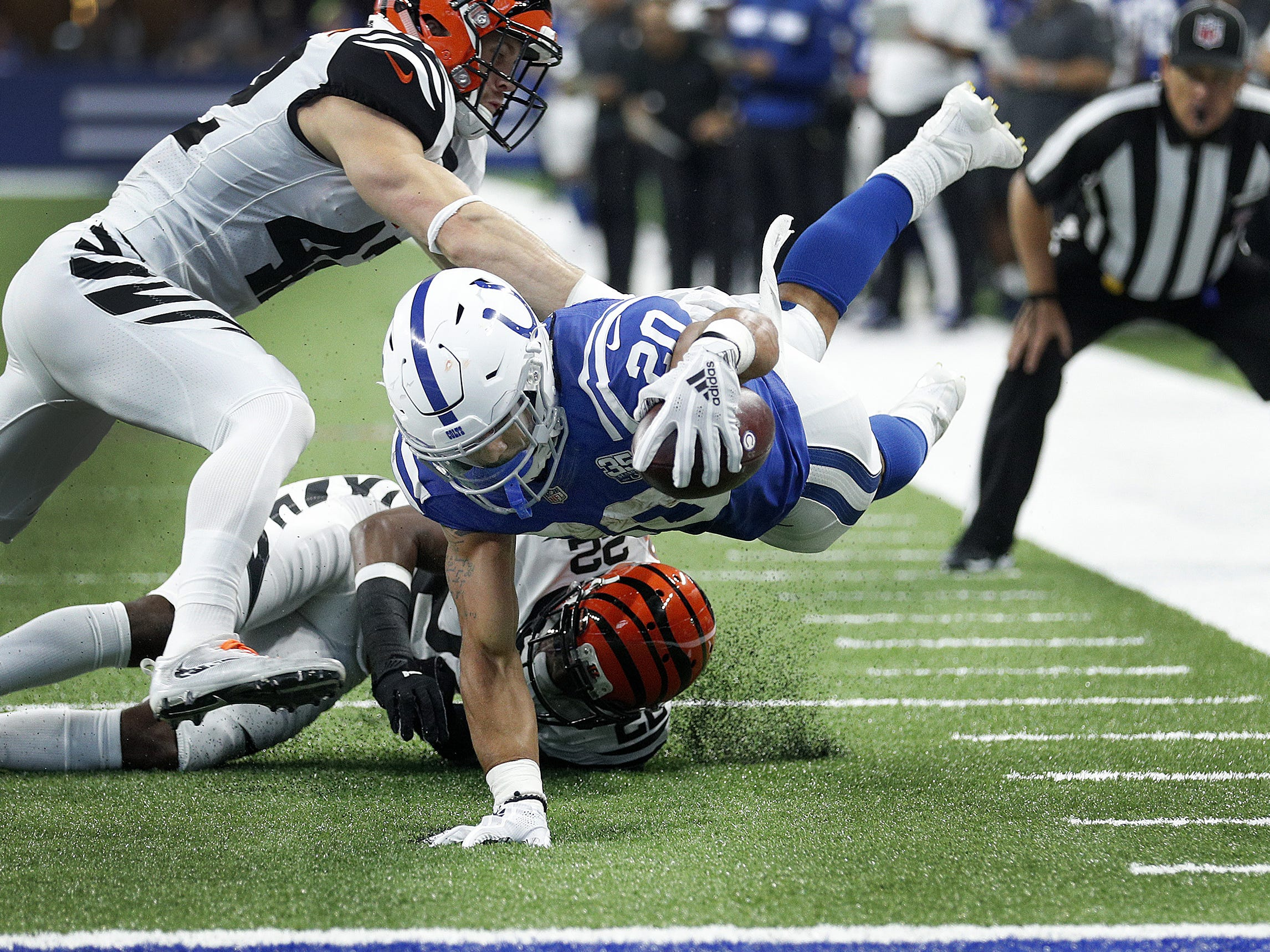 Indianapolis Colts running back Jordan Wilkins (20) reaches for the goal line but is stopped by Cincinnati Bengals safety Clayton Fejedelem (42) and cornerback William Jackson (22) in the first half of their game against the Cincinnati Bengals at Lucas Oil Stadium on Sept. 9, 2018.