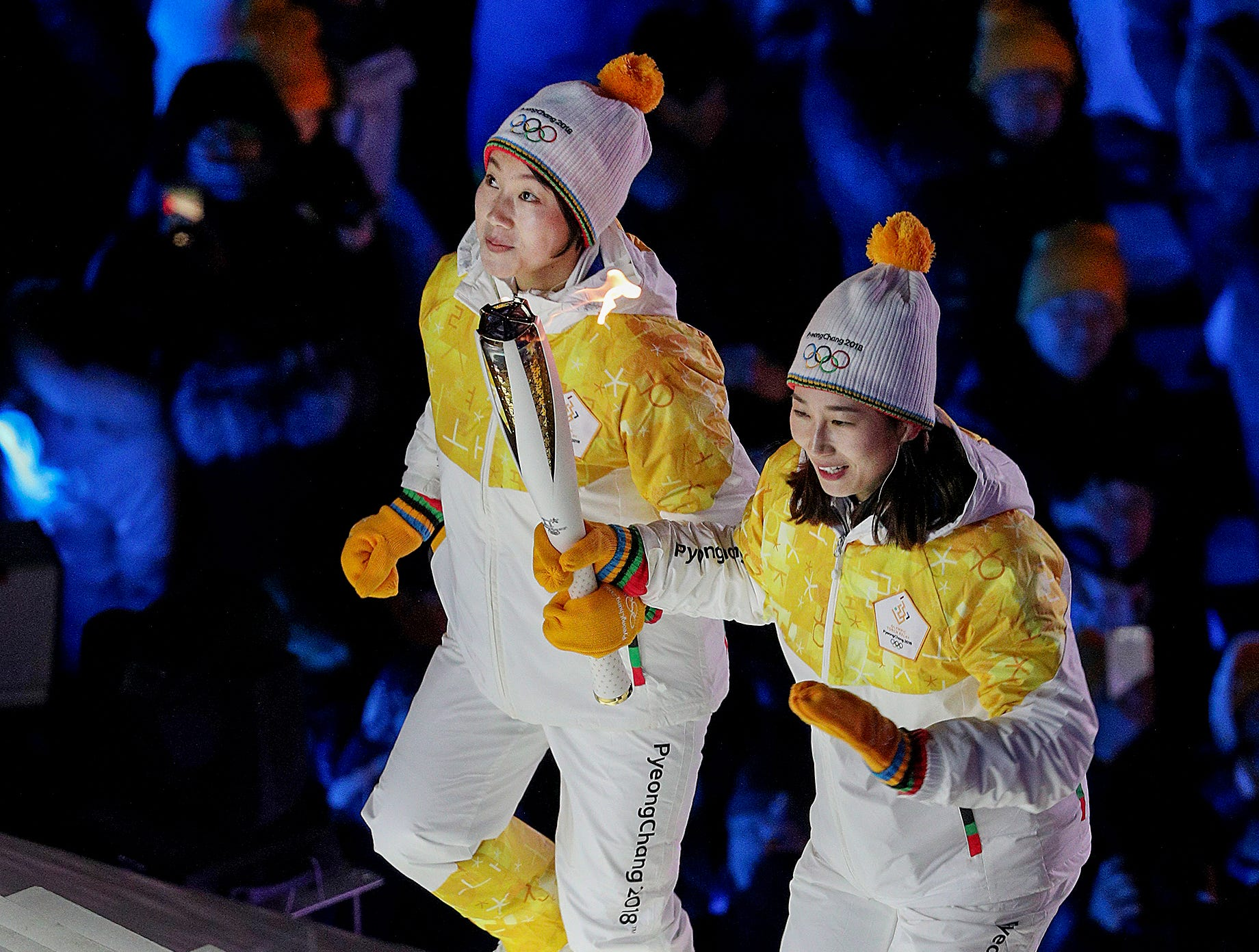 Feb 9, 2018; Pyeongchang, South Korea; A North and South Korean athlete runs the torch up the step to the cauldron during the Pyeongchang 2018 Olympic Winter Games opening ceremony at Pyeongchang Olympic Stadium. Mandatory Credit: Matt Kryger-USA TODAY Sports