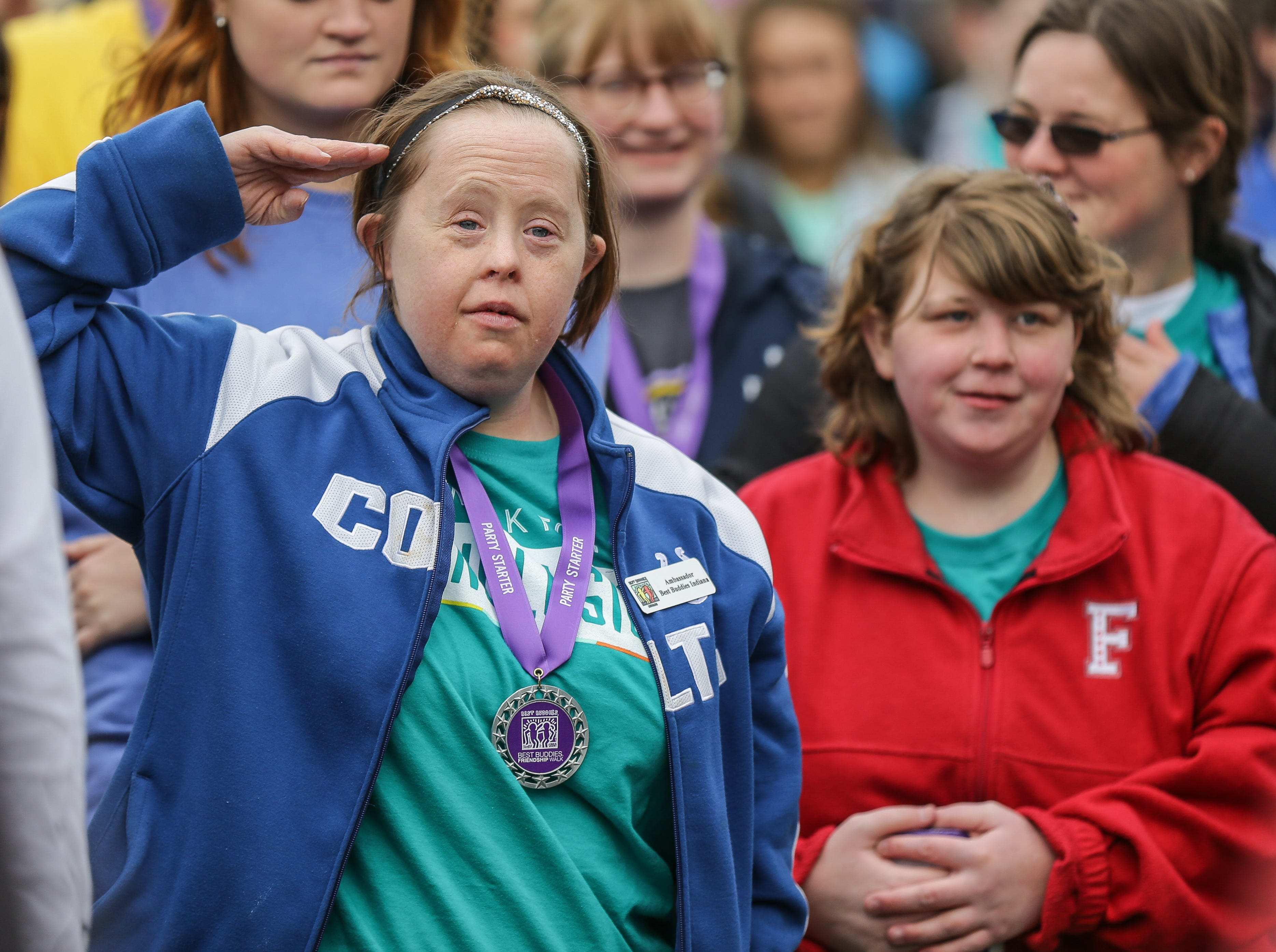 Kylene Webber, left, salutes during the National Anthem while standing next to Annie Wood, right, during the Best Buddies Friendship Walk held at White River State Park in Indianapolis on Sunday, April 22, 2018.