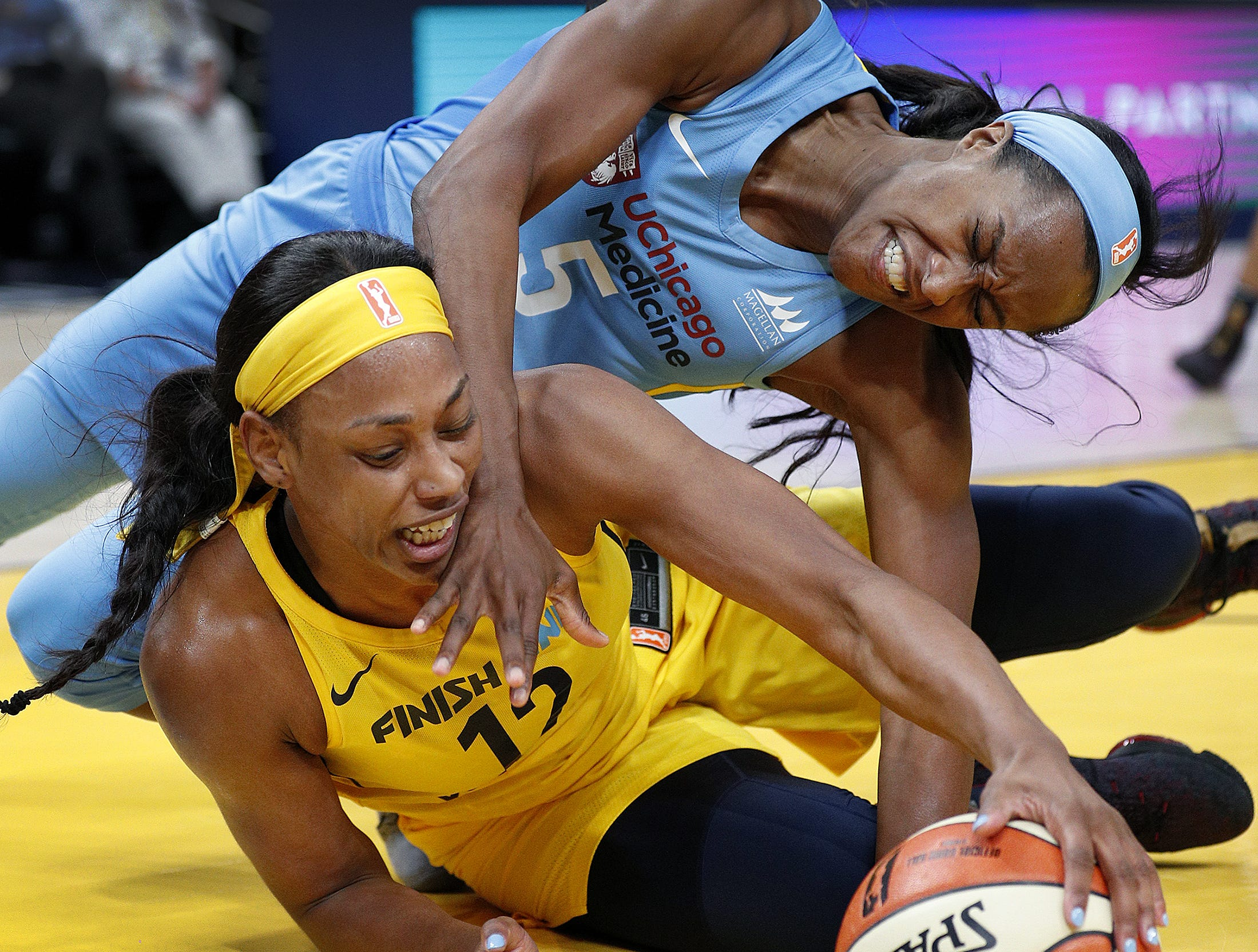 Indiana Fever forward Bashaara Graves (12) fights for a loose ball with Chicago Sky guard Chelsea Hopkins (5) in the first half of their WNBA preseason basketball game at Bankers Life Fieldhouse on Monday, May 7, 2018.