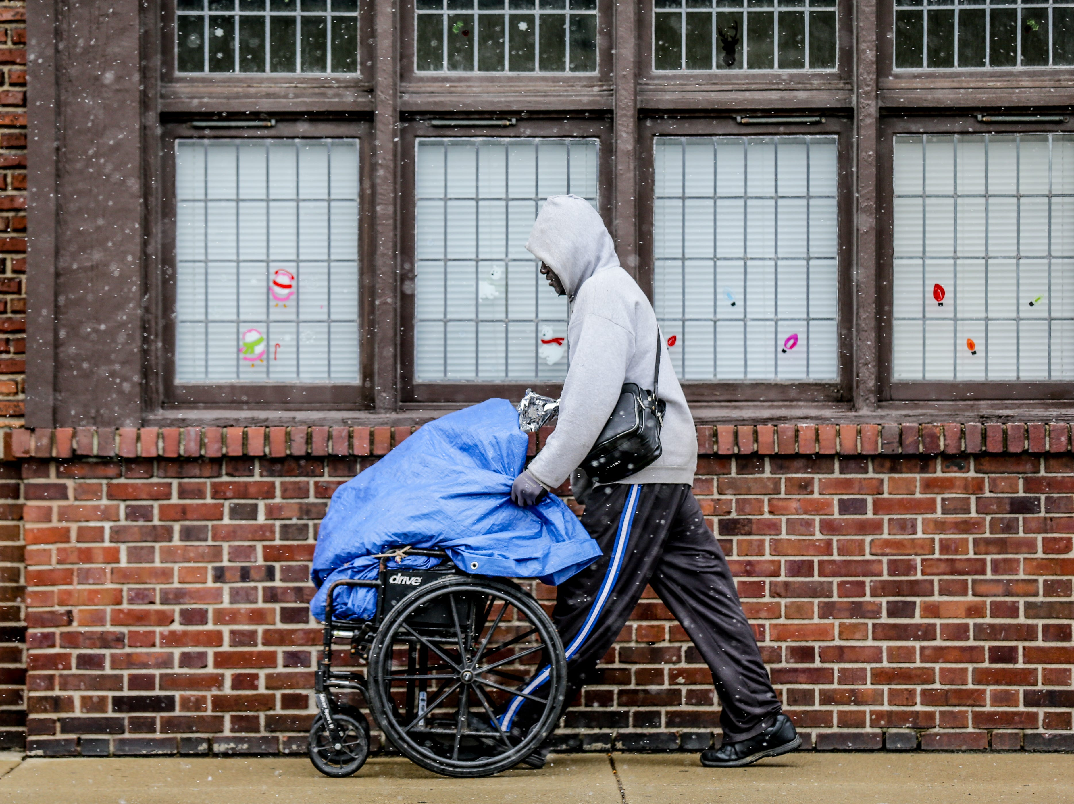 A pedestrian pushes a wheel chair as snow falls in Indianapolis on Monday, April 16, 2018.