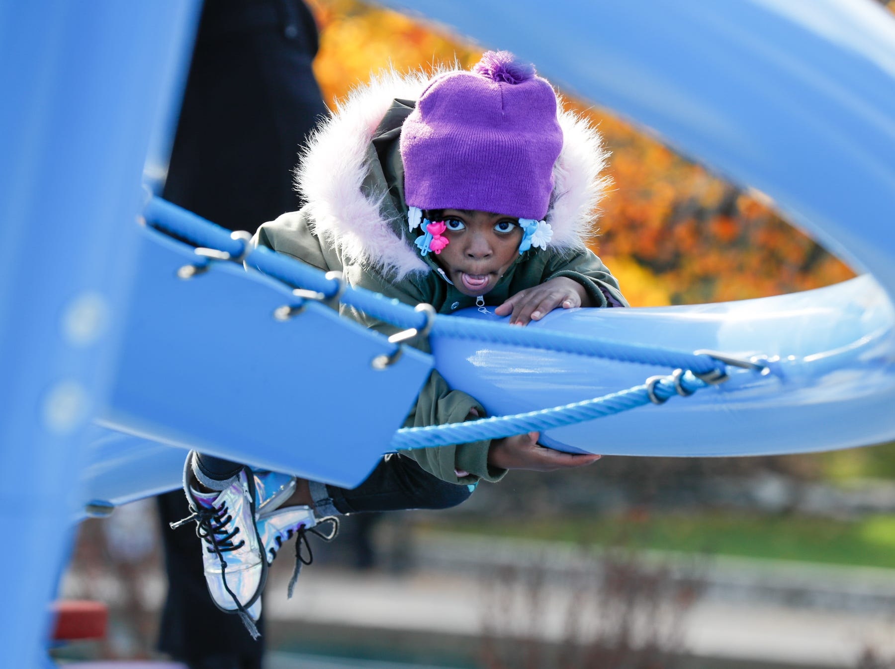 Karter Dycus climbs new playscape equipment during the grand opening celebration of the Colts Canal Play Space in Indianapolis on Thursday, Nov. 8, 2018.