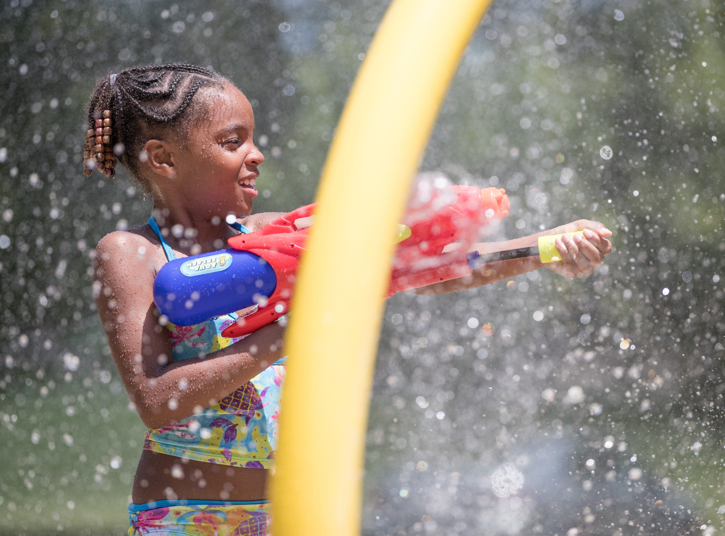Alaiah Walliams sprays her friend with a water gun at  Bertha Ross Park splash pad in Indianapolis on Thursday, June 28, 2018.