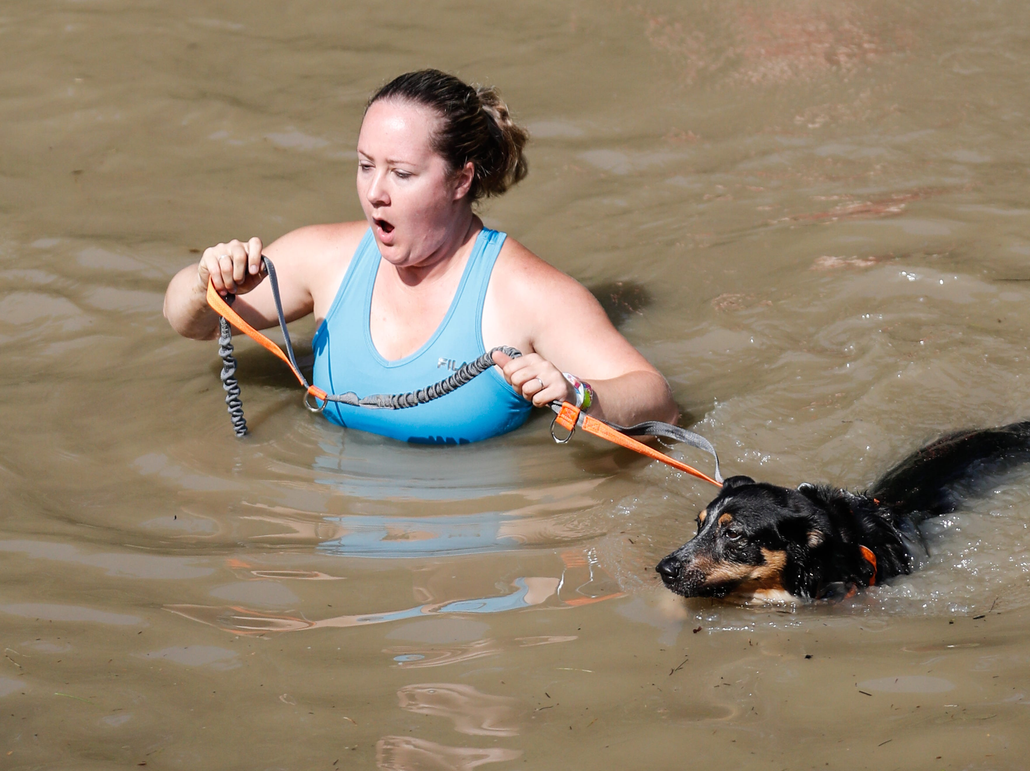 Val Human and her dog Oscar cross a creek during the annual Hollis Adams Mud Run at Camp Sertoma in Indianapolis, on Saturday, June 16, 2018. Funds from the event support the Hollis Adams Foundation.