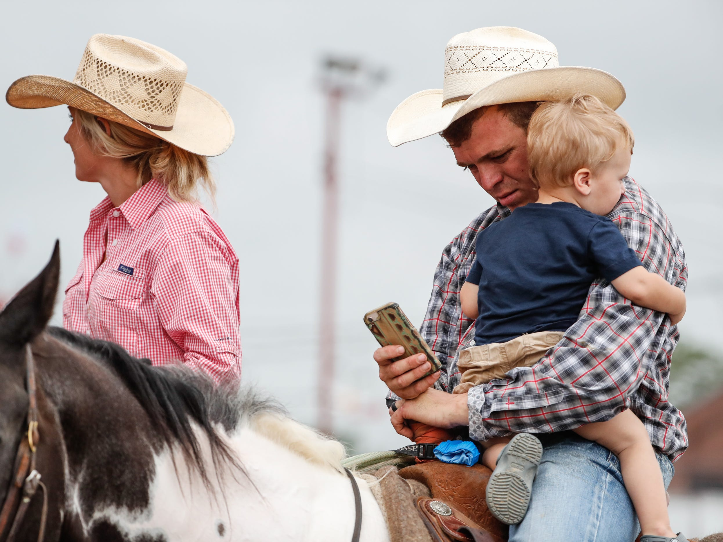 Cowboy Zach Kilgus holds his son Slate next to his wife Alicia Kilgus during the Championship Rodeo at the Indiana State Fair on Wednesday, Aug. 15, 2018.