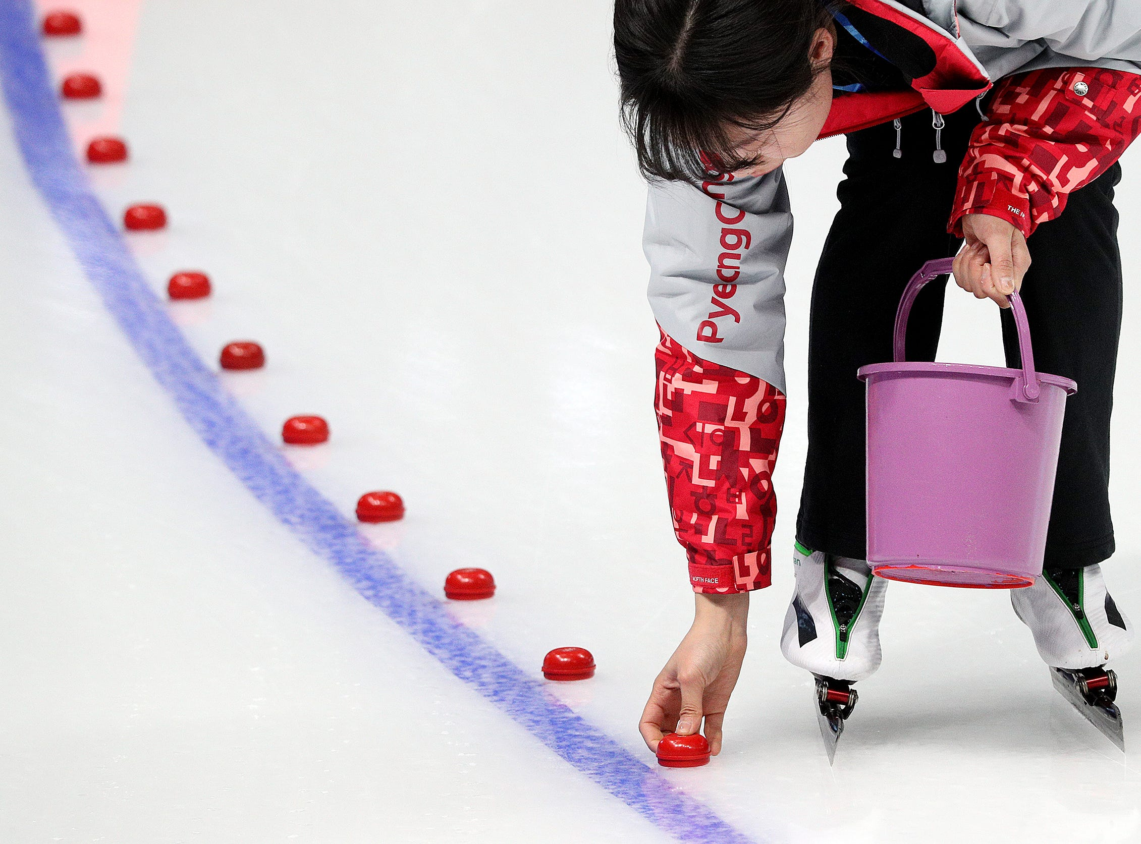 Feb 12, 2018; Pyeongchang, South Korea; An ice track worker puts down the red markers in one of the corners before the start of the Women's 1500km Speed Skating finals at the Pyeongchang 2018 Olympic Winter Games at Gangneung Ice Arena. Mandatory Credit: Matt Kryger-USA TODAY Sports