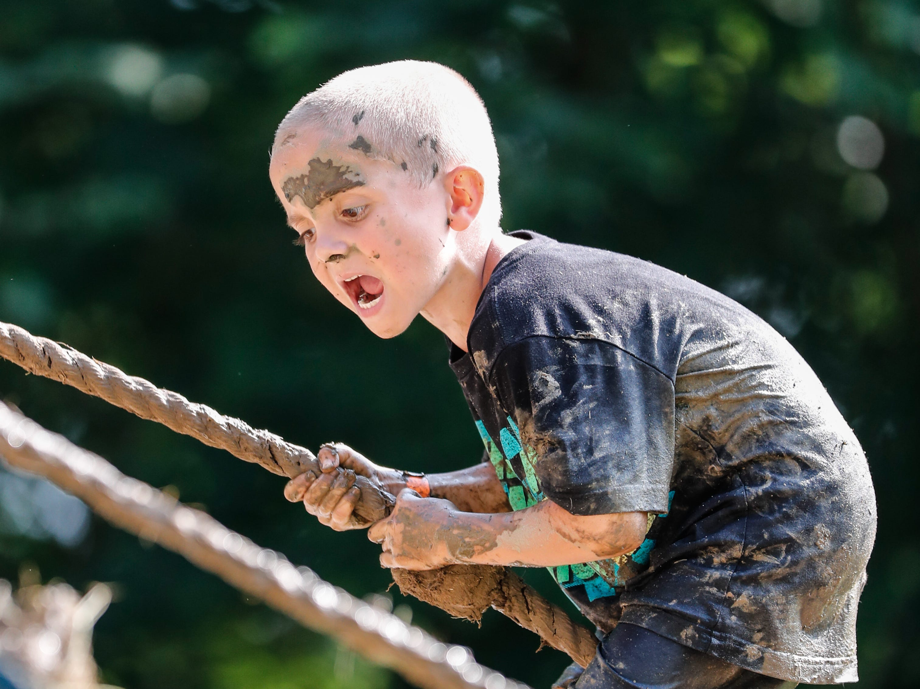L.J. Lewellen lets out a scream while climbing an obstacle during the annual Hollis Adams Mud Run at Camp Sertoma in Indianapolis, on Saturday, June 16, 2018. Funds from the event support the Hollis Adams Foundation.