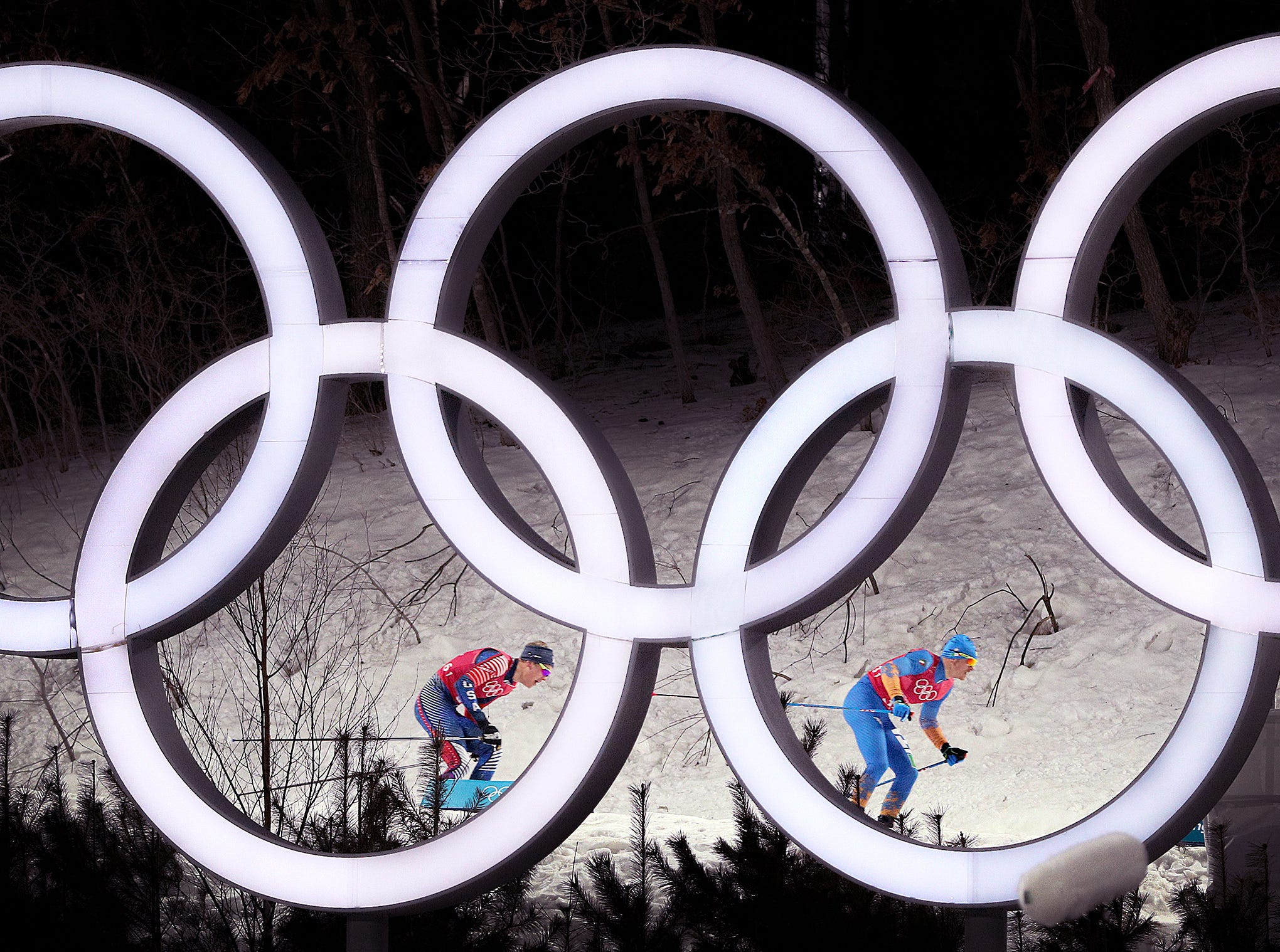 Feb 21, 2018; Pyeongchang, South Korea; Team USA's Erik Bjornsen and Italy's Dietmar Noeckler ski past the Olympic rings during the Men's Team Free Sprint cross-country finals the Pyeongchang 2018 Olympic Winter Games at Alpensia Cross-Country Centre. Mandatory Credit: Matt Kryger-USA TODAY Sports