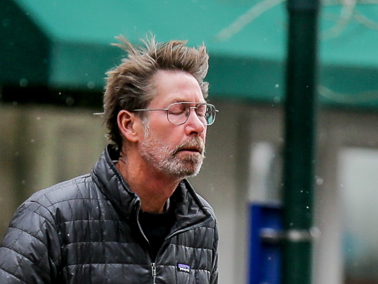 A man is hit in the face with a cold gust of wind and snow fluries in Indianapolis on Monday, April 16, 2018.