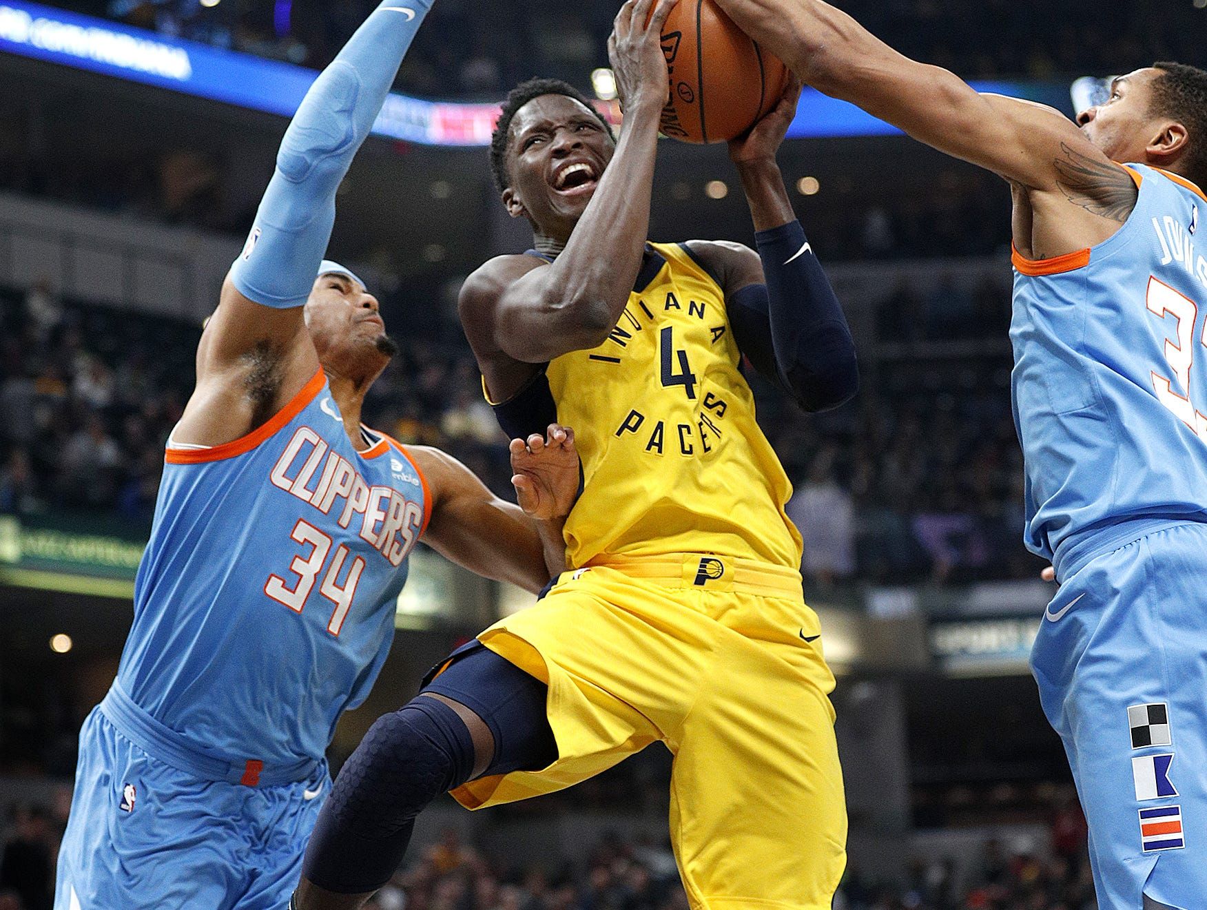 Indiana Pacers guard Victor Oladipo (4) drives by LA Clippers forward Tobias Harris (34) and Wesley Johnson (33) in the first half of their game at Bankers Life Fieldhouse on Friday, March 23, 2018.