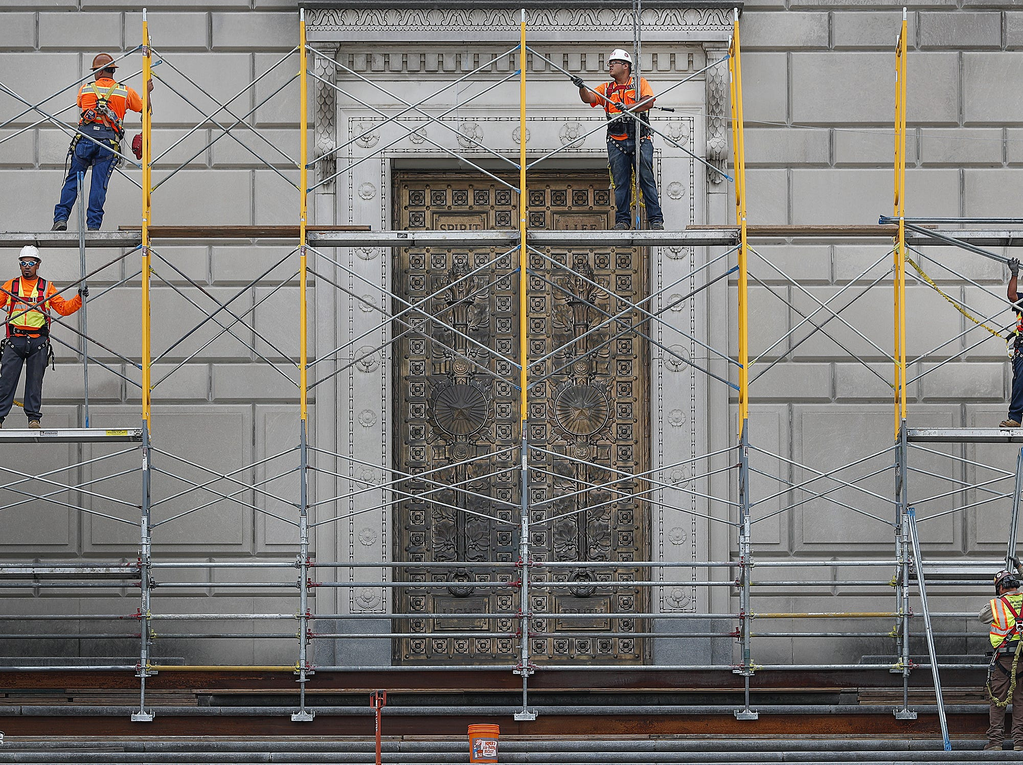 Workers assemble scaffolding around the Indiana War Memorial building for the installation of a new $2.2 million granite and copper roof on the pyramidal dome, or ziggurat, on Monday. Brig. Gen. J. Stewart Goodwin, executive director of Indiana War Memorials Commission, said the project will be completed in November, at which time runners may resume climbing the stairs of the building.