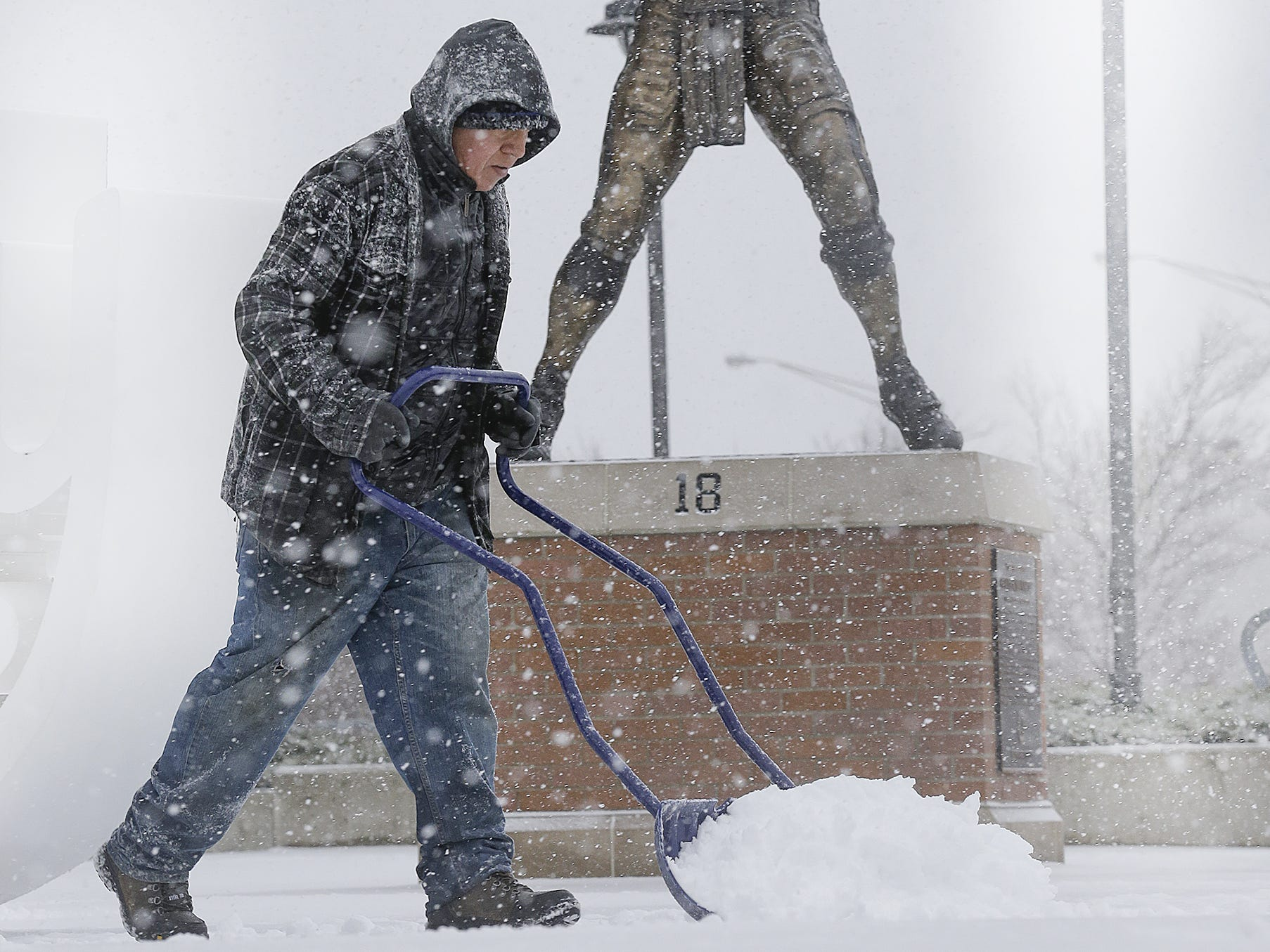 Victor Garcia pushes the snow from the sidewalks and away from the statue of Peyton Manning as he keeps the snow clear from Lucas Oil Stadium. Severe winter weather hit central Indiana with rain turning to ice and the snow Friday, Jan 12, 2018.