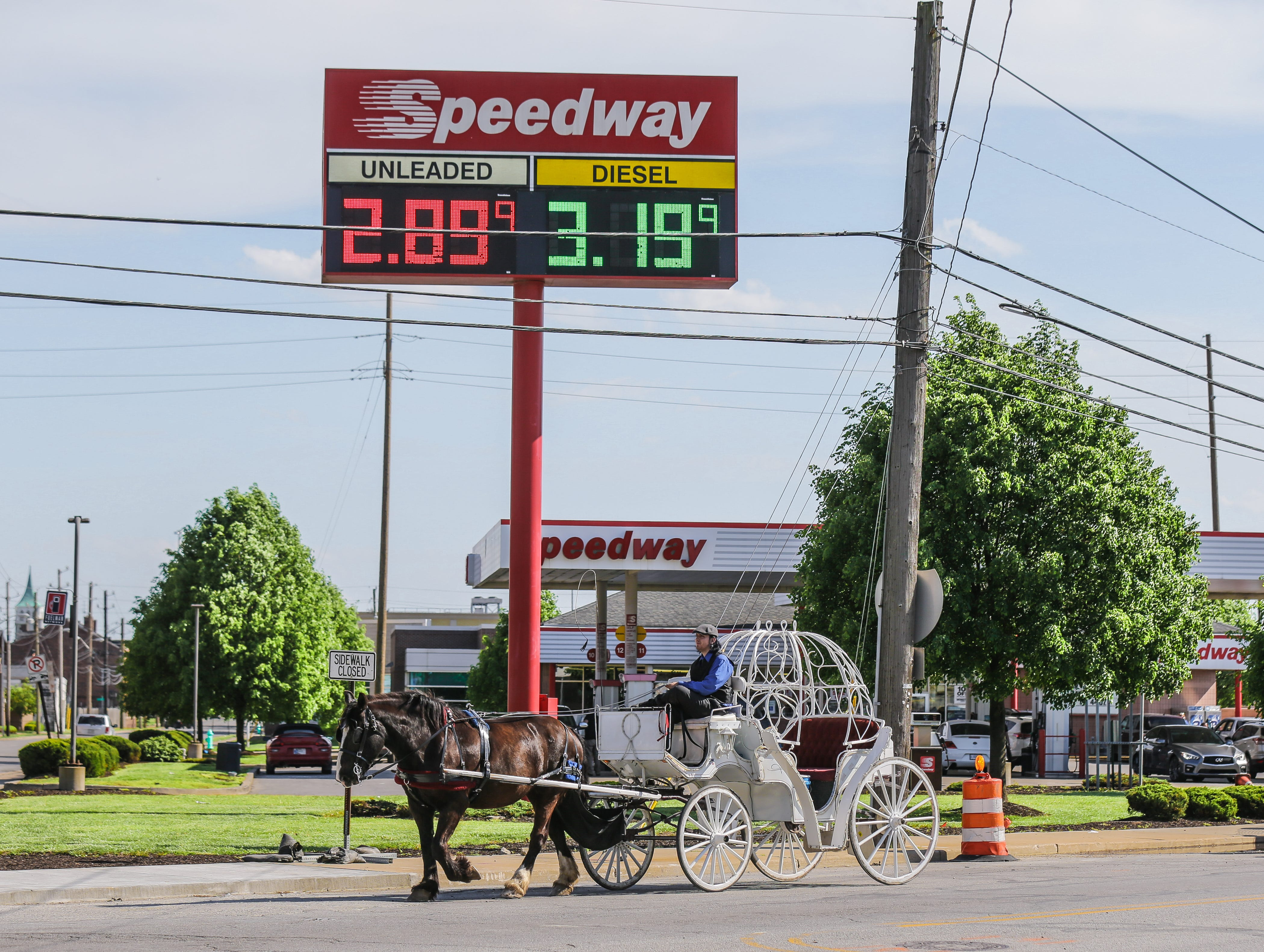 Jake Steinhardt from Blue Ribbon Carriages drives his carriage past the Speedway Gas Station located at 401 S. Kentucky Ave. in Indianapolis on Thursday, May 10, 2018. Gas prices are on the rise in Indiana.