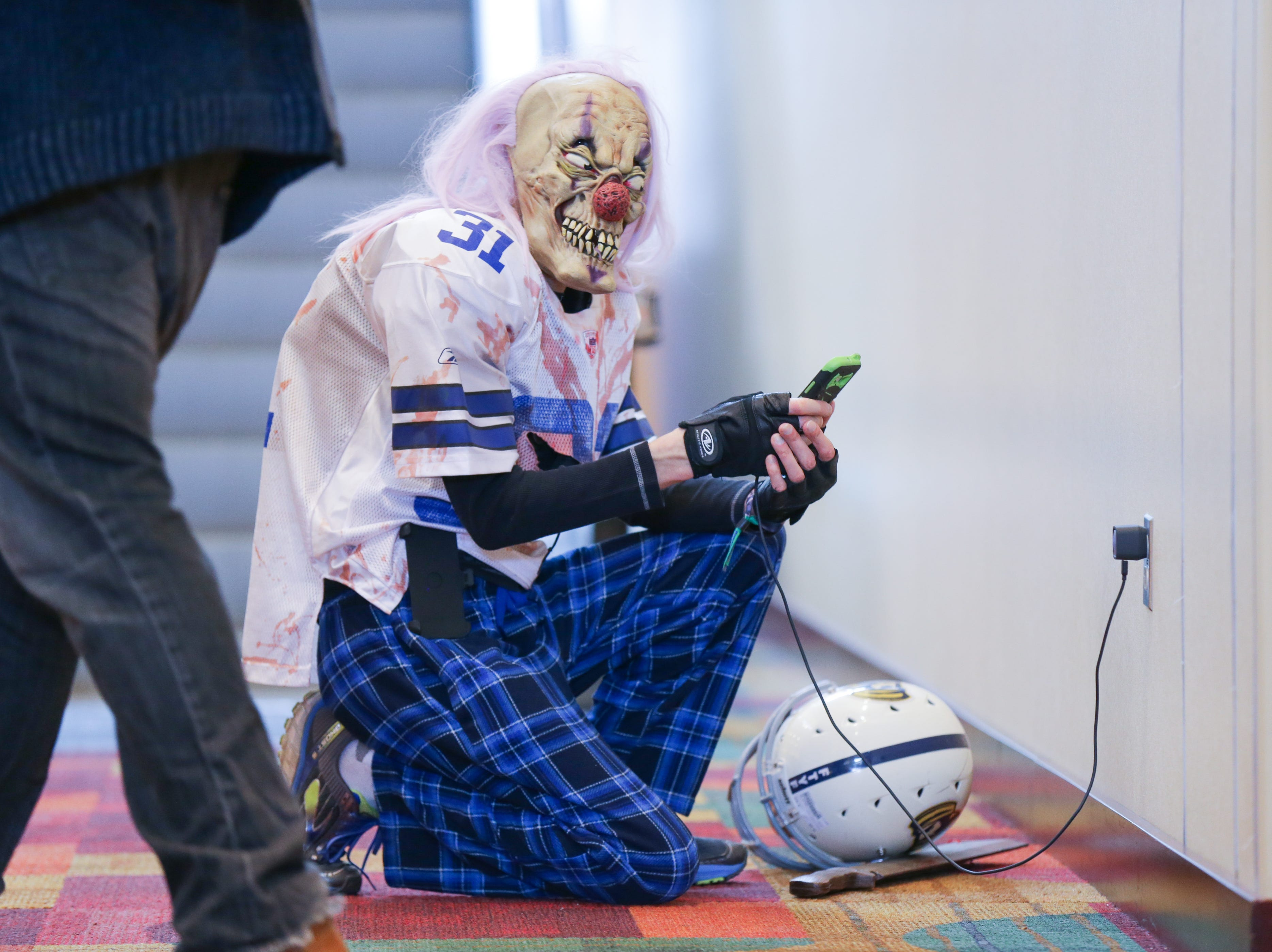 A cosplayer charges their phone at the Indiana Comic Con held at the Indianapolis Convention Center on Sunday, April 1, 2018.