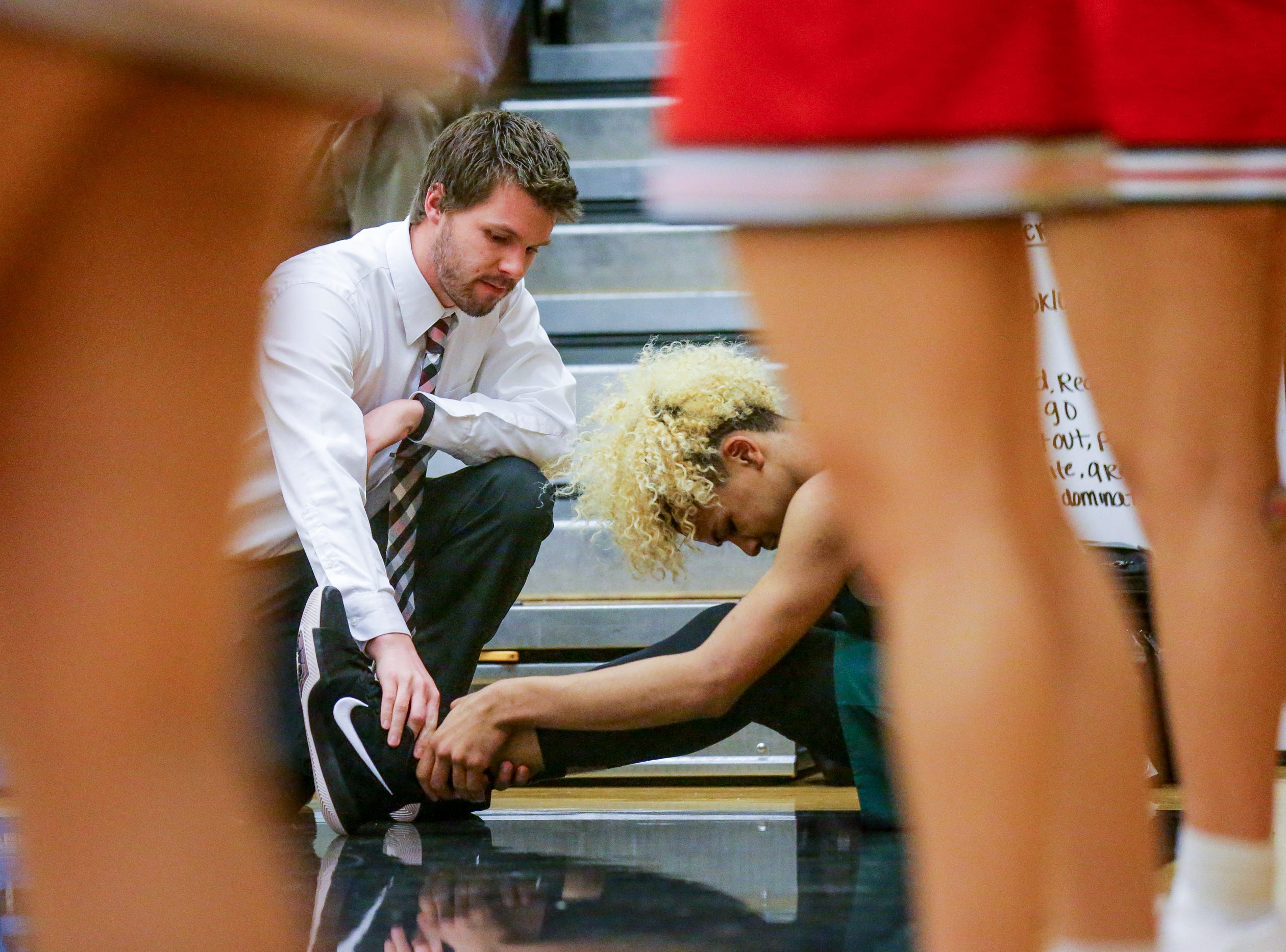 Lawrence North High School guard Mike Saunders (3) is checked out after injuring his ankle on a play during the IHSAA Sectional held at Warren Central High School on Tuesday, Feb. 27, 2018.