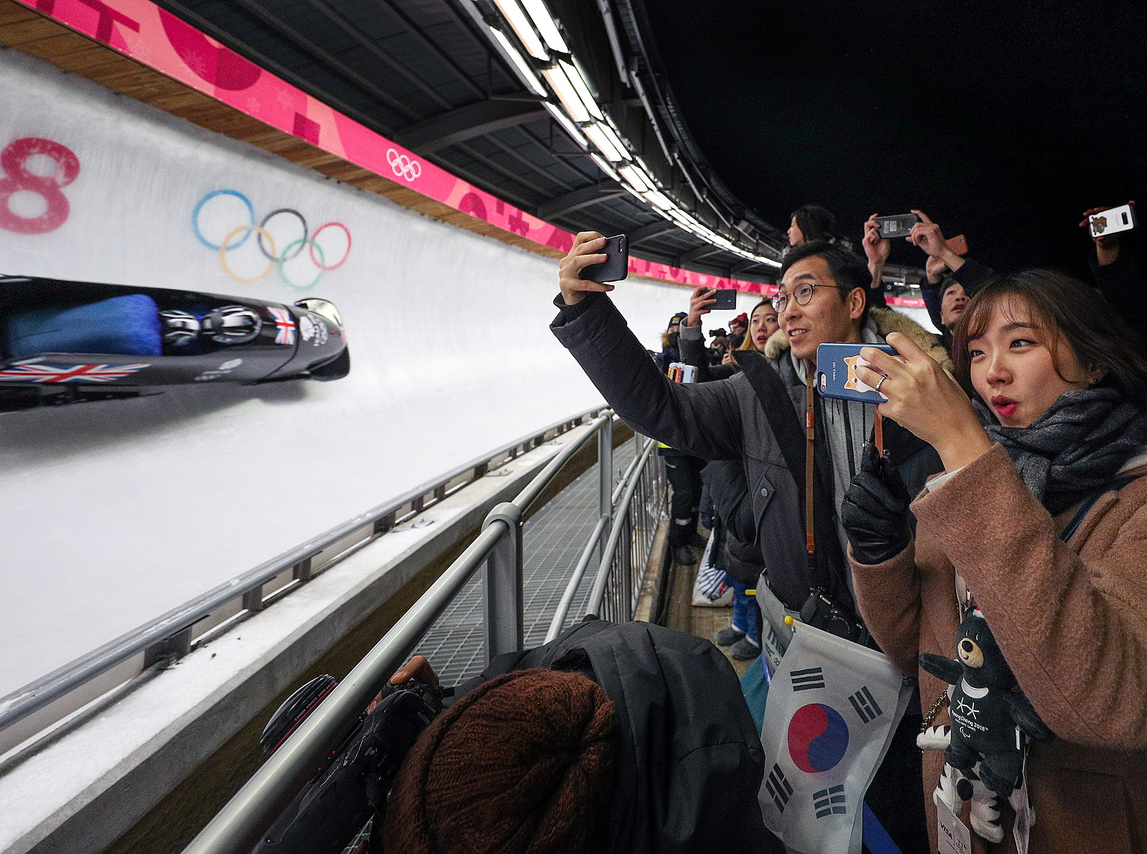 Feb 18, 2018; Pyeongchang, South Korea; Boblsleigh fans watch as Great Britain's Brad Hall and Joel Fearson round turn #14 during the Bobsleigh Mens 2-Man Competition Run 1 at the Pyeongchang 2018 Olympic Winter Games at Olympic Sliding Centre. Mandatory Credit: Matt Kryger-USA TODAY Sports