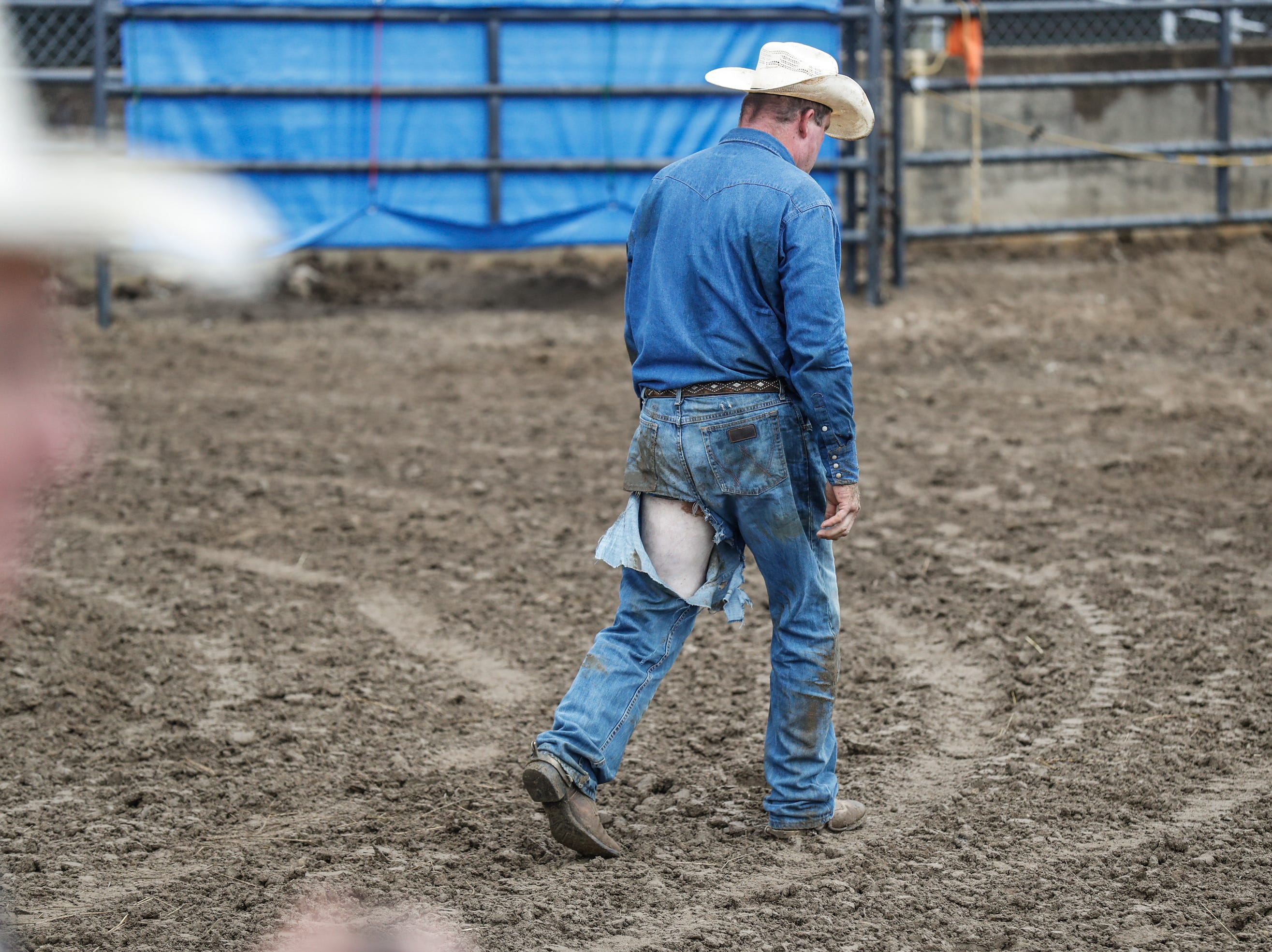 Jesse McPike looses part of his jeans while competing in the steer wrestling competition during the 3 Bar J Rodeo Company's Championship Rodeo at the Indiana State Fair on Wednesday, Aug. 15, 2018.