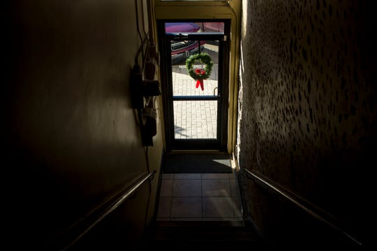 Looking down the main flight of steps a Christmas wreath decoration can be seen in the window at Area Relief Ministries in Jackson, Tenn., on Monday, Dec. 17, 2018.