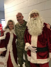 Jason Strawn, who has been deployed for the past six months, stands alongside Mrs. Claus (Felicia Reeves) and Santa Claus (Clayton Quinn) after the Claus's delivered Strawn as a Christmas present to his sons Austin, 12, and Archer, 5, at Decaturville Elementary School.