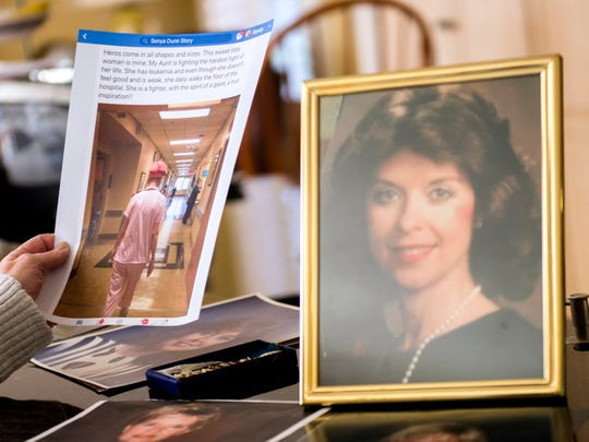 Sandy Dunn holds a printout of a Facebook post showing Jean Nance walking around the hospital, left, next to portrait of Nance on the counter of Dunn's Alcoa home.
