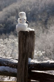 A small snow man sits on the post of a split rail fence like a tribute to snow at a over look on the Gatlinburg bypass.