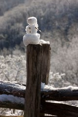 A small snow man sits on the post of a split rail fence like a tribute to snow at a over look on the Gatlinburg bypass.A snowstorm that dropped up to 2 inches of snow across East Tennessee has left icy roadways and most school systems closed today.The National Weather Service is calling for more snow showers over the next two days with as much as 2 inches of new accumulation through Wednesday.