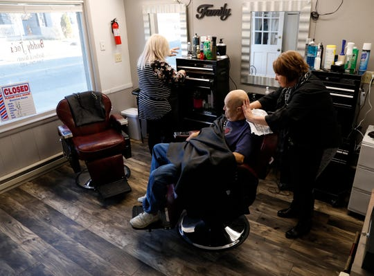Angela Francis, right, massages Charles Matthews neck Tuesday morning, at Buddy Joe's Barber and Beauty Shop on East Sixth Avenue in Lancaster as Rebecca Brown arranges her station at the shop.