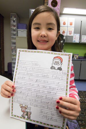 7-year-old Mika Felkins holds her letter to Santa Monday, Dec. 17, 2018, one of the assembled letters Spencer Elementary second grade teacher Tammy Ferguson had her class write to be sent to Saint Nick.