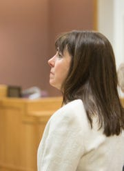 Judge Theresa Brennan faces a television monitor showing the live feed of Genesee County Judge G. David Guinn during her arraignment Tuesday, Dec. 18, 2018 on felony charges.