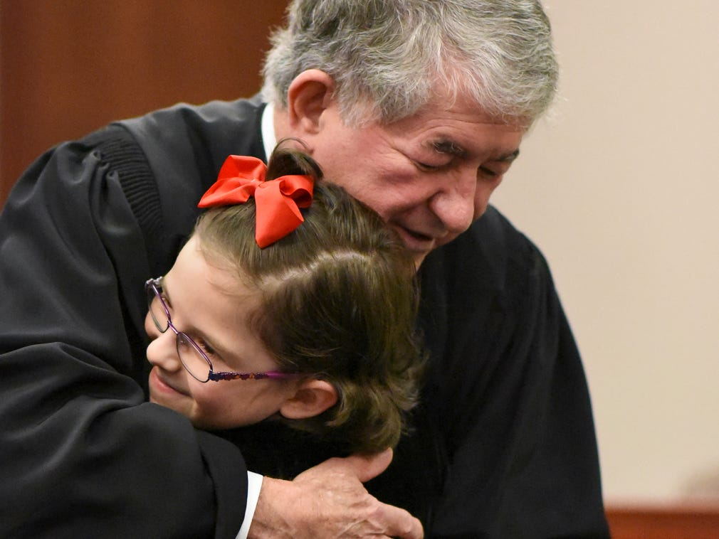 "Layla Suarez of Leslie hugs Ingham County Probate Judge George Economy after he made her adoption official Tuesday, Dec. 18, 2018.  ""I asked for a dad,"" Layla answered after Economy asked what she wanted for Christmas.  Economy has done adoption week 32 of his 33 years on the bench."