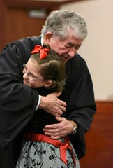 Layla Suarez of Leslie hugs Ingham County Probate Judge George Economy after he made her adoption official Tuesday, Dec. 18, 2018.