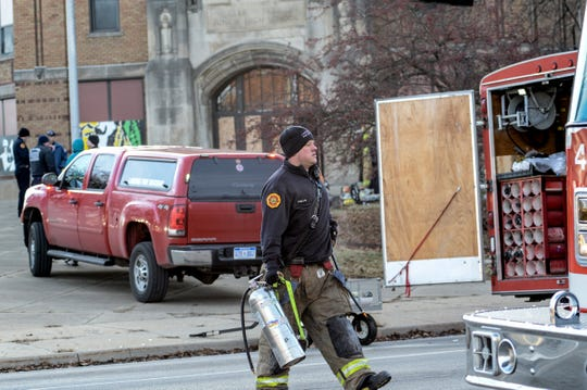 A Lansing firefighter returns an air tank at the site of a fire at the Walter French Building Tuesday, Dec. 18, 2018.