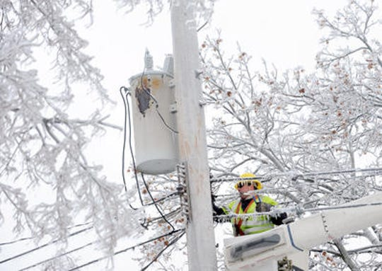 Dave Dora, a lineman from Grand Haven Board of Light and Power, works on fallen wires shortly after an ice storm hit Lansing in December 2013.