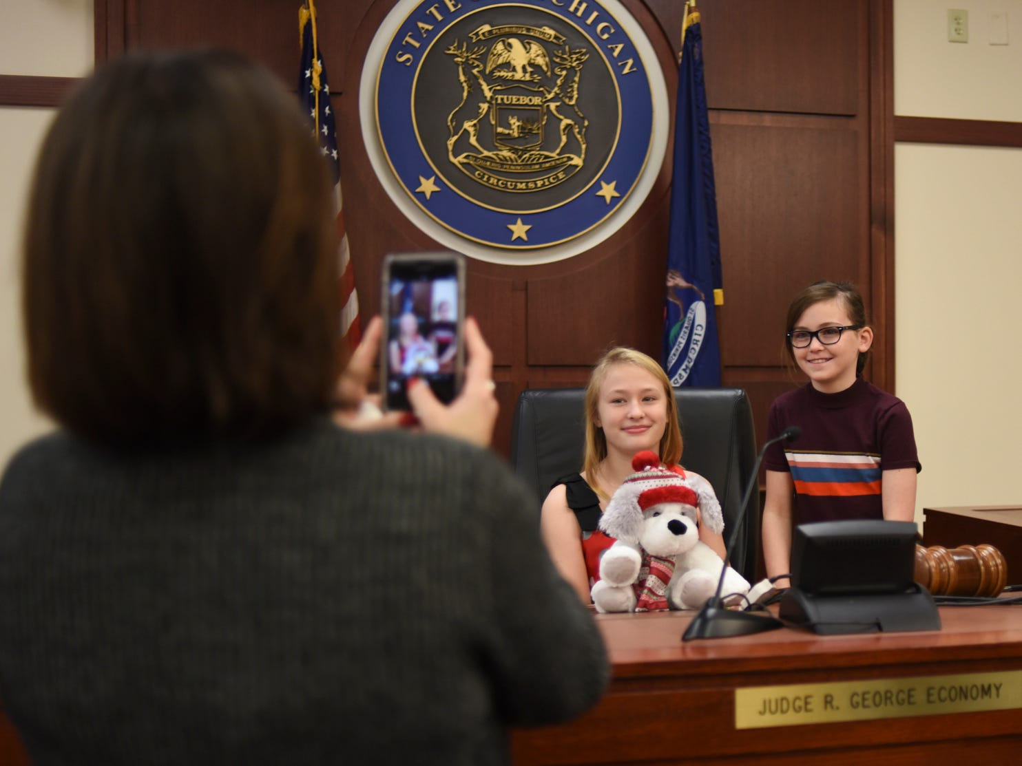 Ava Miller, 10, middle, gets her picture taken with friend Lucy Rose Boland, 9,  while seated at Ingham County Probate Judge George Economy's bench, Tuesday, Dec. 18, 2018, at Veterans Memorial Courthouse in Lansing.  Economy ordered Ava's adoption official.   He has done adoption week 32 of his 33 years on the bench.