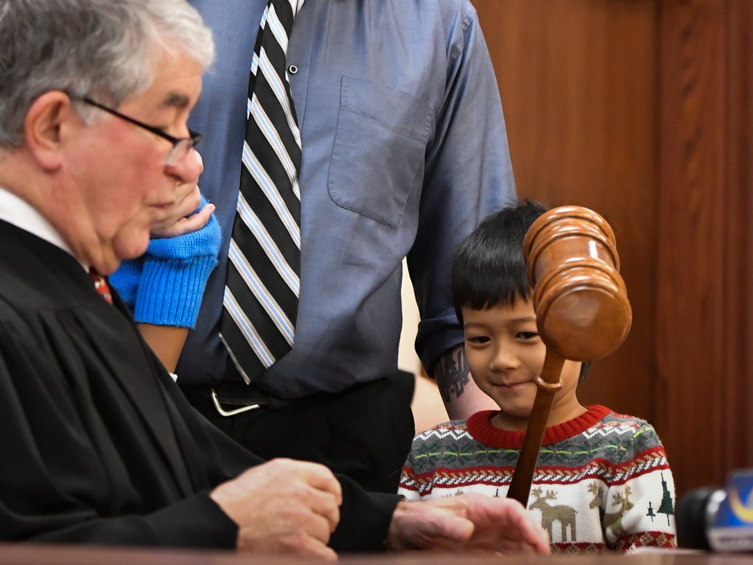 Five-year-old Nathanael Blakely of Mason, gets a chance to use Ingham County Probate Judge George Economy's special Christmas gavel during a hearing that made his and 2-year-old brother Owen's adoptions official, Tuesday, Dec. 18, 2018, at Veterans Memorial Courthouse in Lansing.  Economy has held adoption week 32 of his 33 years on the bench.  Also pictured is the boys' dad Mark.