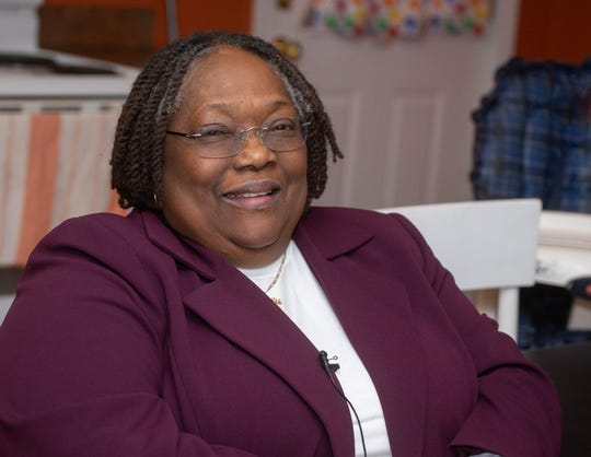 Dr. Joan Jackson Johnson, known as Lansing's advocate for the poor, waits Dec. 12, 2018 for the family to arrive at their new home through the One Church One Family program she administers.