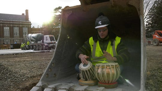 "MSU College of Music student Sebastian Buhts plays the tabla inside a construction scoop during the filming of the ""Carol of the Bells"" video."