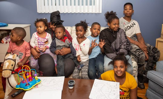 The Osborne Family, left to right, Richard, 3, Rihanna, 2, Lakiva, mother, O'shea, 1, Zyionya and Charles, 7, Laniya, 11,  Omarion, 12, and Neveah, 9 down in front.