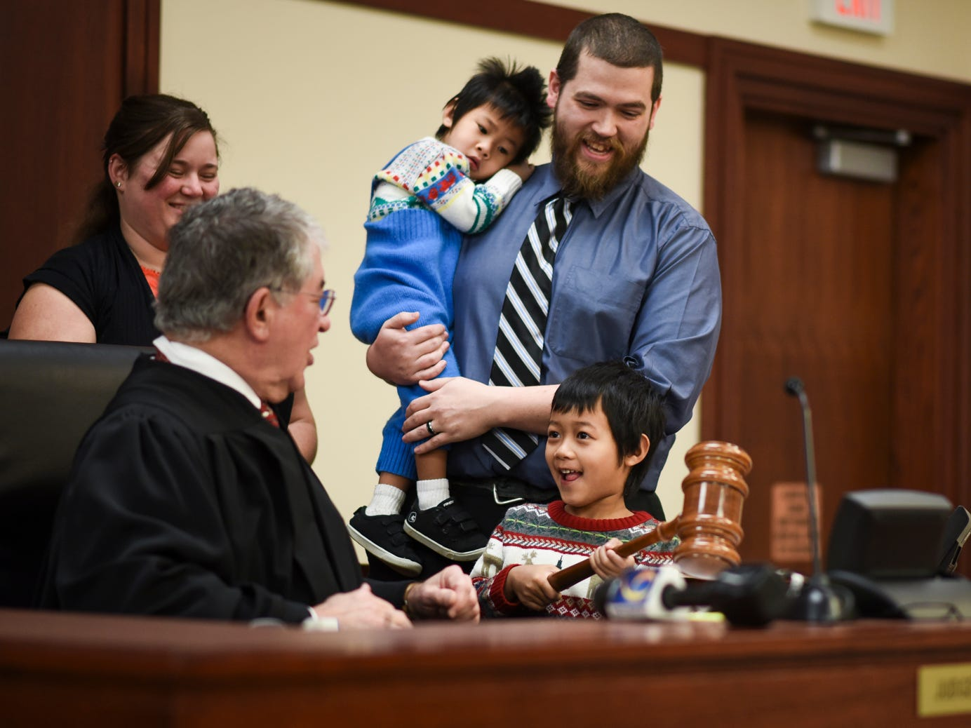 Five-year-old Nathanael Blakely of Mason, gets a chance to use Ingham County Probate Judge George Economy's special Christmas gavel during a hearing that made him and 2-year-old brother Owen's adoptions official, Tuesday, Dec. 18, 2018, at Veterans Memorial Courthouse in Lansing.  Economy has held adoption week 32 of his 33 years on the bench. Economy is retiring at the end of the year. Also pictured are Mark and Emily, the boys' parents.