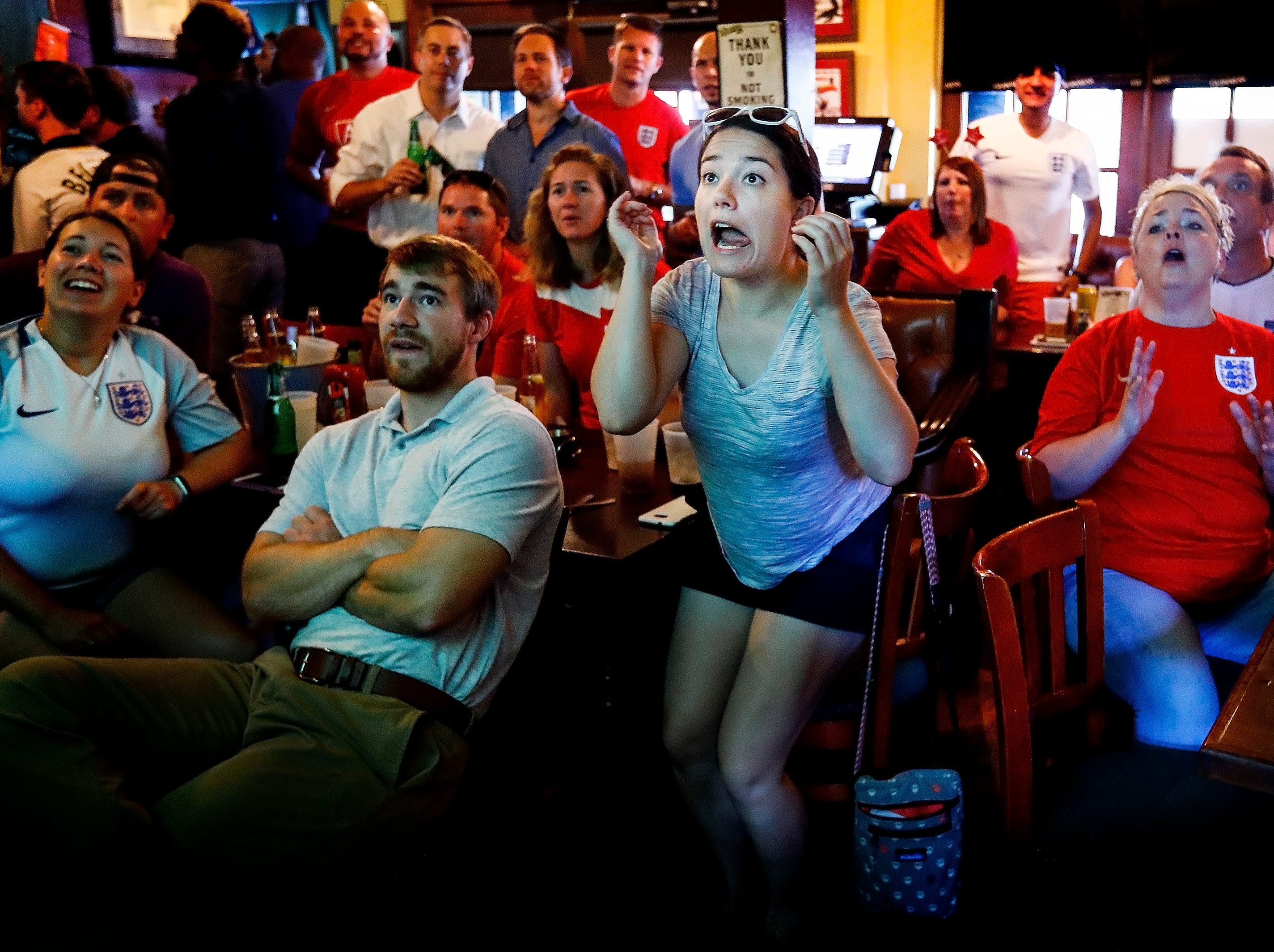 English National Soccer team fan Kate Schuhlein (middle) reacts after a missed goal attempt against Croatia, while fans enjoy the World Cup match at Celtic Crossing.