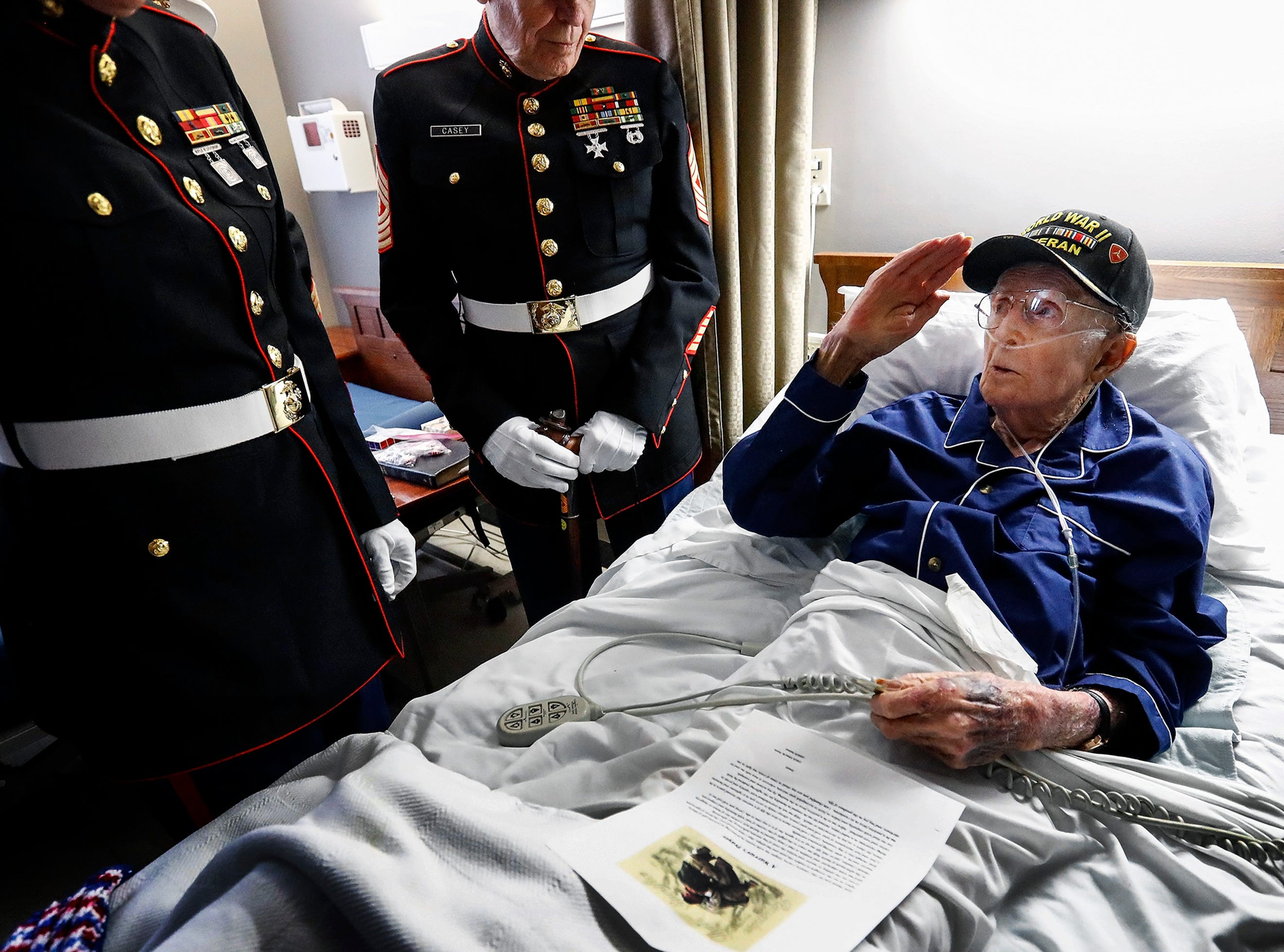 """Pfc. Robert """"Buck"""" Arata, 95, salutes fellow Marines who visited him at the Applingwood Healthcare Center, an assisted-living home where he now lives. Arata, who will celebrate his 96th birthday in late March is the Mid-South's last surviving marine to fight in The Battle of Iwo Jima during World War II. As part of the 9th Marine Regiment, Arata, landed on Iwo Jima's beaches three-days after D-Day on Feb. 22, 1945."""