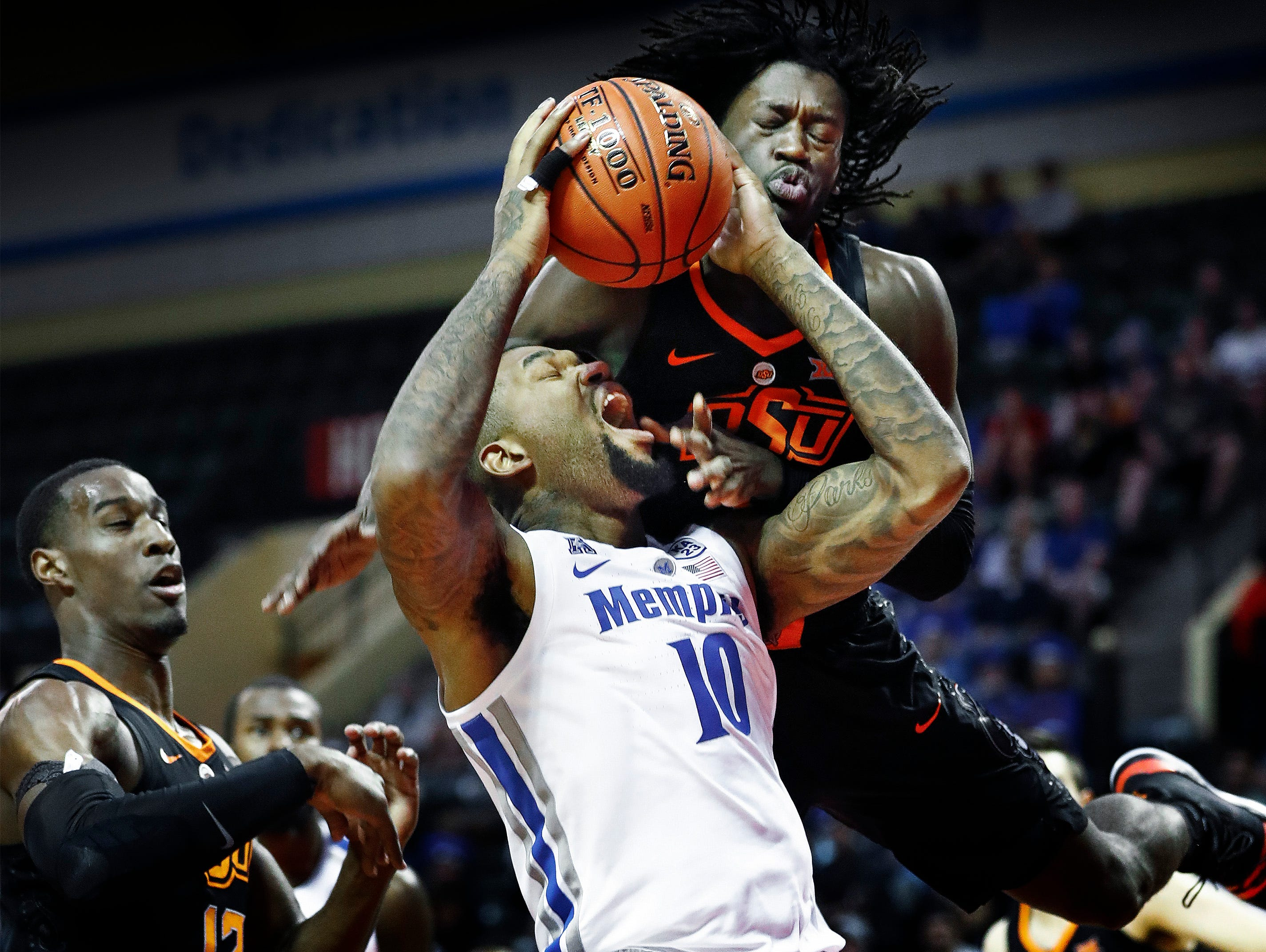 Memphis forward Mike Parks Jr. (bottom) is fouled by Oklahoma State defender Isaac Likekele (top) during first round action in the Advocate Invitational in Orlando Thursday, November 22, 2018.